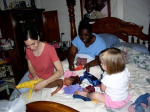 Alexis, Gloria, and Abbey playing dolls on Gloria's bed.
